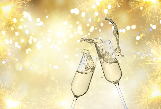 Two festive champagne glasses on golden bokeh background with lights and fireworks