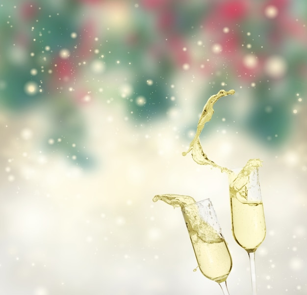 Two festive champagne glasses on green and silver bokeh background with snowfall