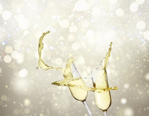 Two festive champagne glasses on silver bokeh background with lights
