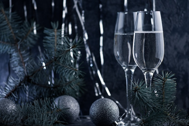 Two festive christmas glasses of champagne on a dark background. new year party