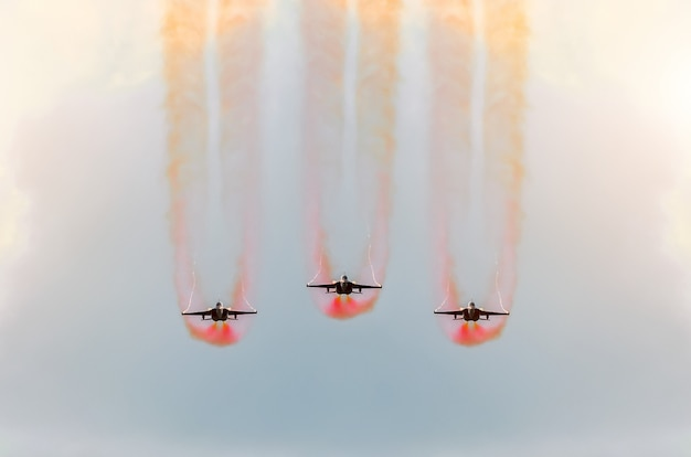 Two fighter jets fly together with red smoke.