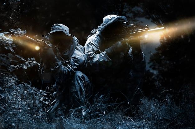 特別ユニットの2人の戦闘機が夜に森の中を移動します。特殊作戦、nato、戦争の概念。ミクストメディア