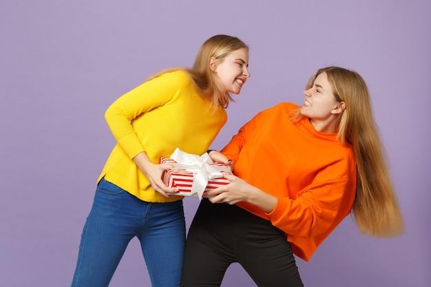 생생한 옷을 입고 싸우는 두 금발 쌍둥이 자매 소녀는 보라색 파란색 벽에 고립 된 선물 리본이 달린 빨간색 줄무늬 선물 상자를 개최합니다. 사람들이 가족 생일, 휴가 개념.