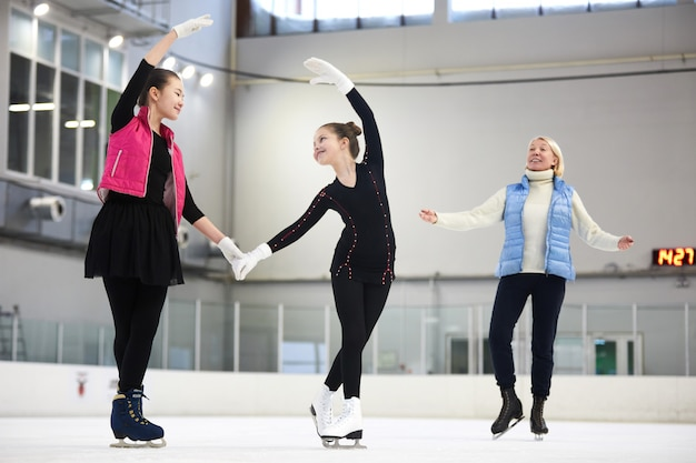 Two figure skaters training with coach