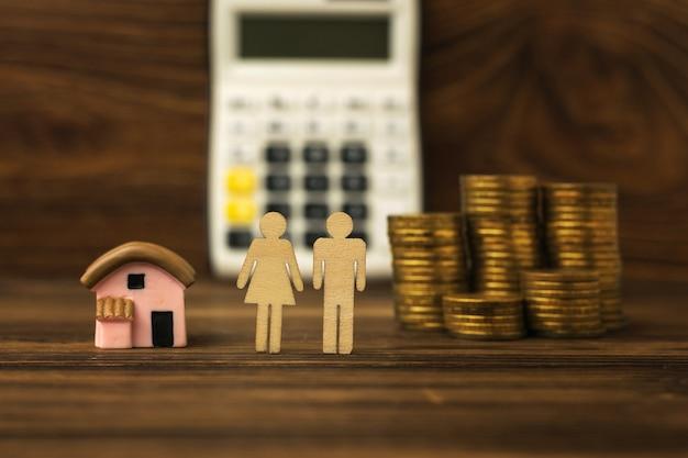 電卓の背景にある2人の人物、家とコイン。住宅取得の概念。モーゲージ。