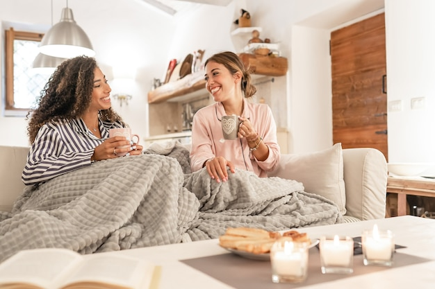 Две прекрасные молодые женщины сидят на диване с одеялом на ногах и смеются, наслаждаясь дома зимой, пьют чай с выпечкой - домашний образ жизни пары женщин-смешанных рас