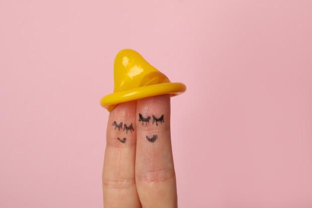 분홍색 표면에 얼굴과 콘돔을 만족시키는 두 손가락
