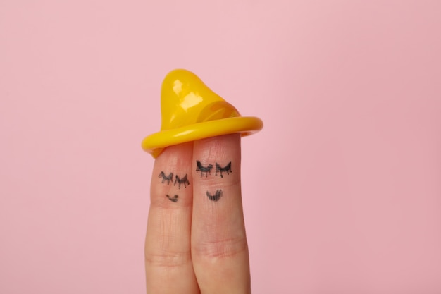 Two fingers with satisfy faces and condom on pink surface
