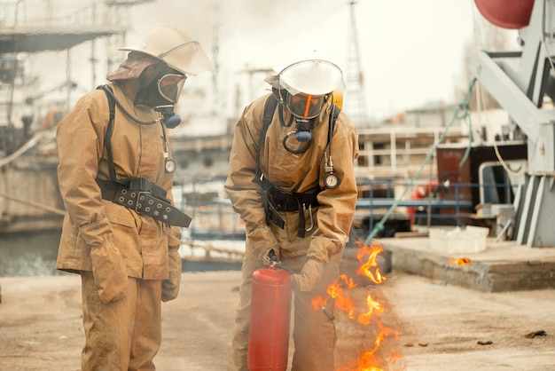 Two firefighters in masks and equipment on a training how to put out the fire