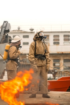 Two firefighters use teamwork on a training how to stop fire in a dangerous mission and protect the environment
