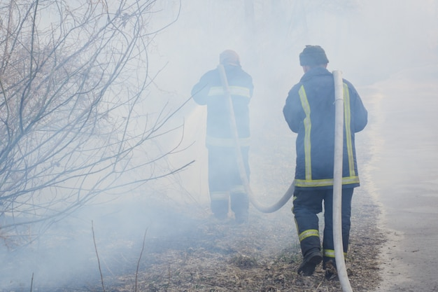 Two fireman in smoke battle forest fire. brave firefighter goes into smoke to put down a wild fire, other fireman holds and carry hose