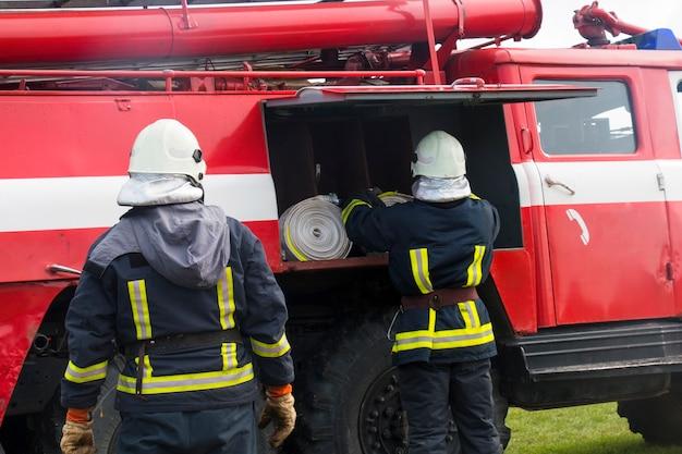 消防車の近くの2人の消防士