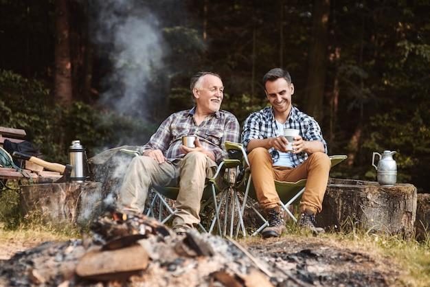 森でキャンプする2人の漁師