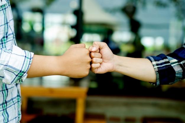 2つの拳のチームワークの団結人々がチームオフィスビジネスでプロジェクトを成功させたときの拳の隆起を示す2つの手のクローズアップ。