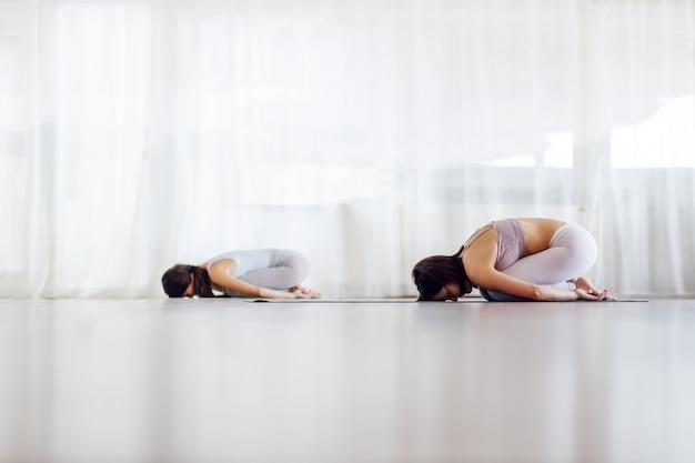 Две женщины-йоги подходят в позу детской йоги. интерьер студии йоги.