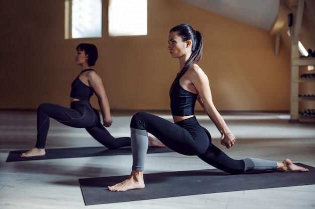 膝のヨガのポーズでトカゲを着た2人の柔軟なヨギ女性。ヨガスタジオのインテリア。