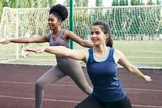 두 맞는 웃는 젊은 여자가 유연성을 향상시키기 위해 스트레칭 운동과 다리 확장을 하 고 공원에서 함께 운동.
