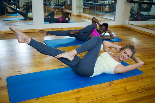 マットの上でストレッチ運動をしている2人のフィット女性