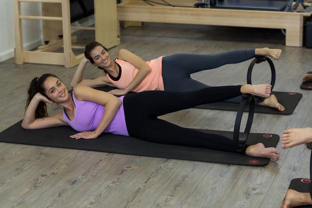 Две подходящие женщины тренируются с кольцом для пилатеса