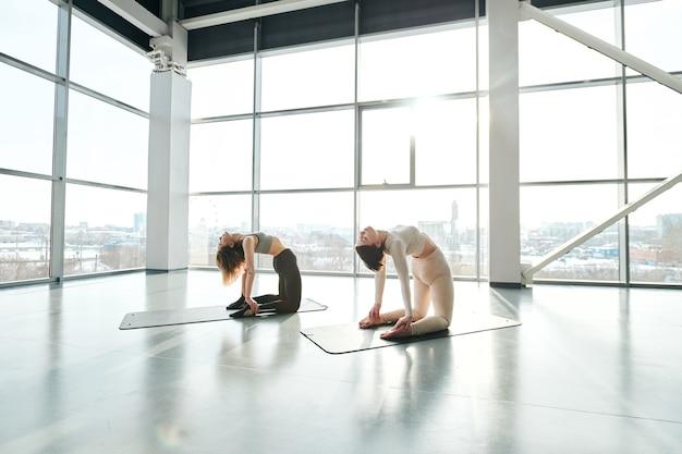 Две подтянутые молодые девушки в спортивной одежде стоят на коленях и наклоняются назад во время занятий йогой на ковриках.