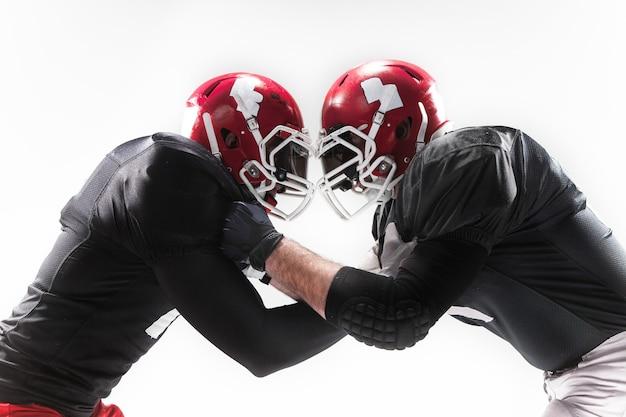 I due uomini di forma fisica come giocatori di football americano che combattono su priorità bassa bianca