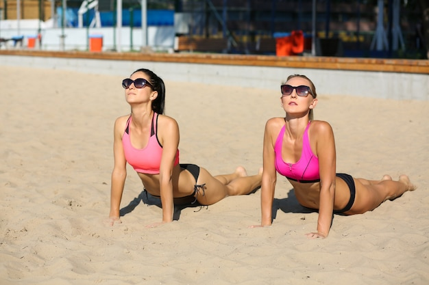 Two fitness models wearing glasses and swimsuit practicing yoga together at the beach