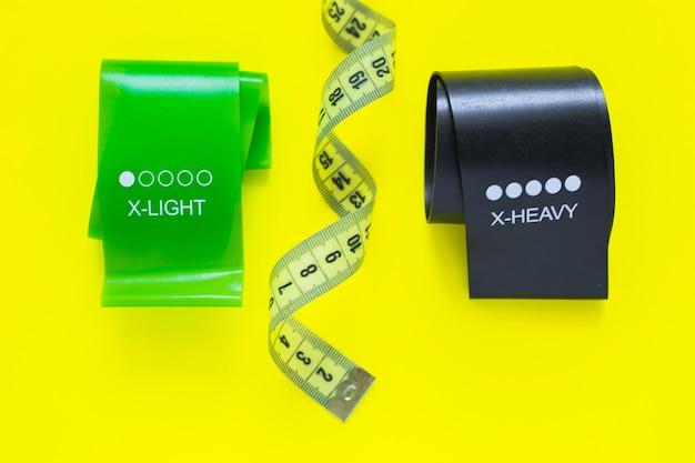 黒と緑の色の2本のフィットネステープが黄色の背景の写真の上部にあります...