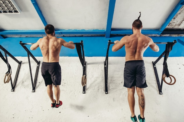 Two fitness toes to bar men pull-ups tree bars workout exercise at gym