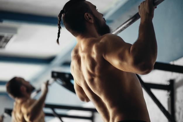 ジムで男性のプルアップツリーバートレーニング運動を禁止する2つのフィットネスつま先