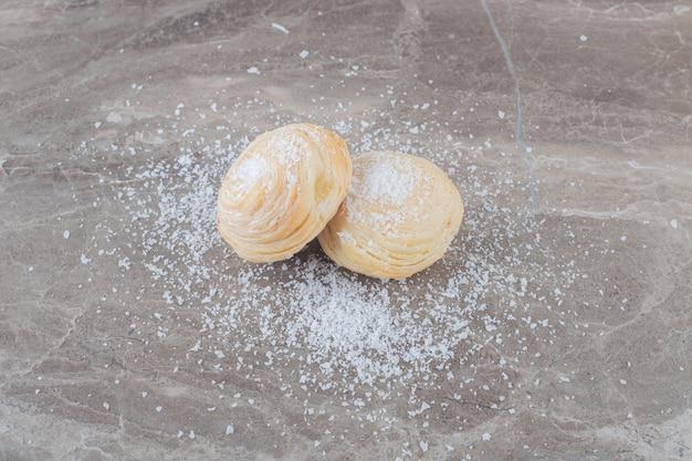 大理石の表面にバニラパウダーでコーティングされた2つのフレーク状のクッキー