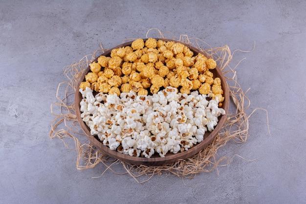 Два вкуса попкорна подаются на деревянном подносе, украшенном соломой на мраморном фоне. фото высокого качества
