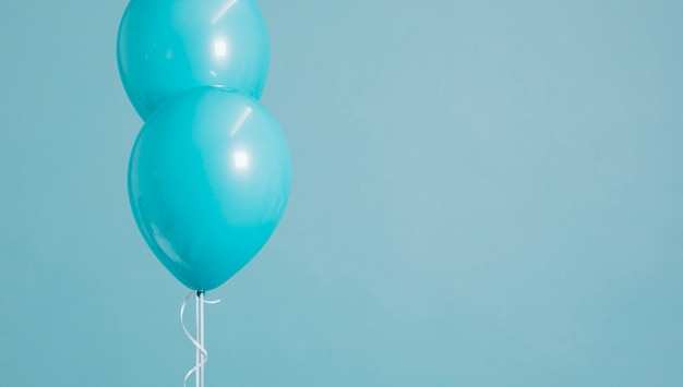 Two floating pastel blue balloons