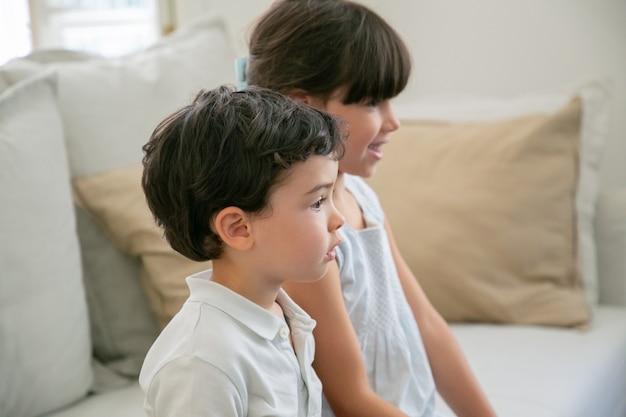 Двое сосредоточенных детей смотрят телевизор дома, сидят на диване в гостиной и смотрят в сторону.