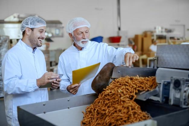 Два сфокусированных инспектора в белой форме и сетках для волос оценивают качество еды. оба одеты в белую форму и имеют сетки для волос. интерьер пищевого завода.