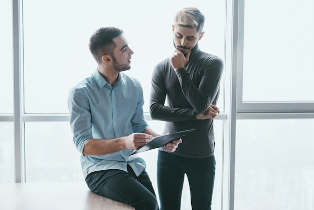 Two focused male coworkers deep in discussion together while standing in a modern office