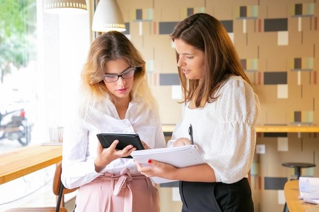 디자인에 대한 새로운 아이디어를 찾는 두 명의 집중된 여성