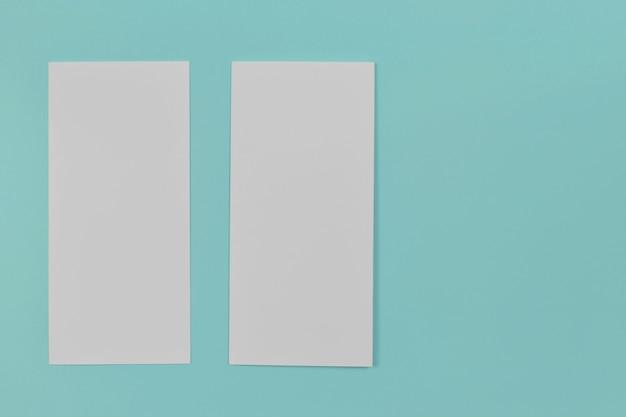 青い背景の2つの折り畳まれた白紙のチラシ折りたたまれた現実的な白紙の紙のモックアップ
