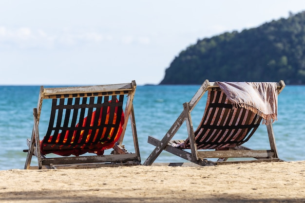 Two folding chairs on the beach with sea and bright sky in the background at koh mak in trat, thailand.