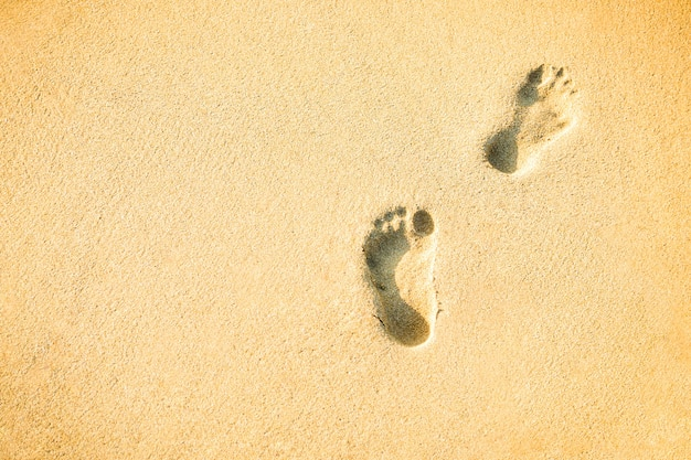 Two footprints on the sand with copy space textured background