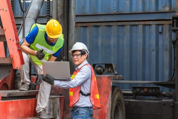 Два мастера с ноутбуком проверяют позицию загрузки контейнеров с грузового судна при транспортировке грузовых контейнеров