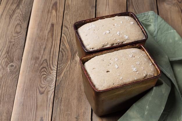 Две формы сырого ржано-пшеничного хлеба с мучной закваской и зеленым полотенцем на столе.