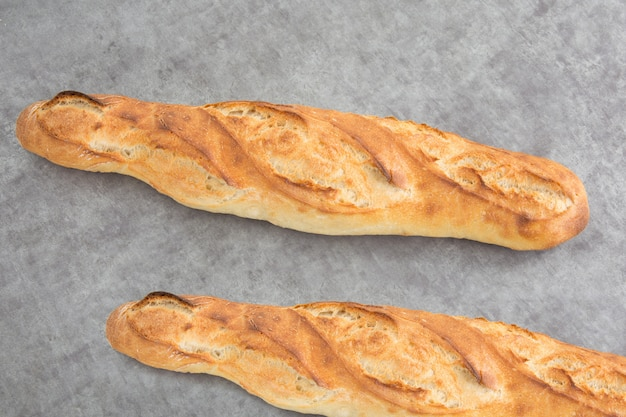 Two french baguettes on a grey