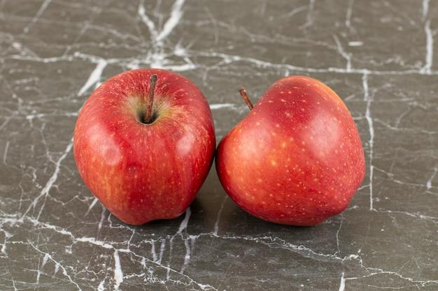灰色の石に2つの新鮮なリンゴ。