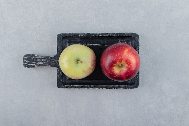 Two fresh apples on black cutting board.