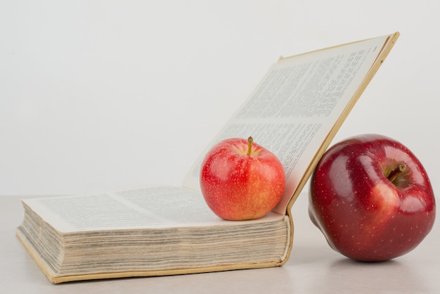 Два свежих яблока с книгой на белом столе.