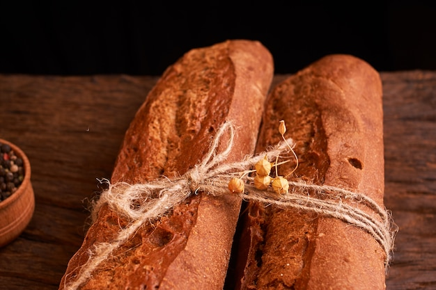 Two fresh baguettes on dark wooden table. selective focus