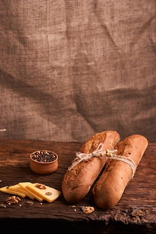 Two fresh baguettes on dark wooden table