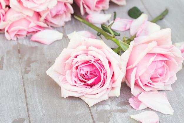 나무 테이블에 누워 두 신선한 피 핑크 장미