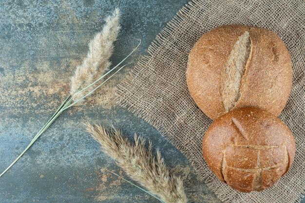 Две свежие коричневые булочки с пшеницей на вретище