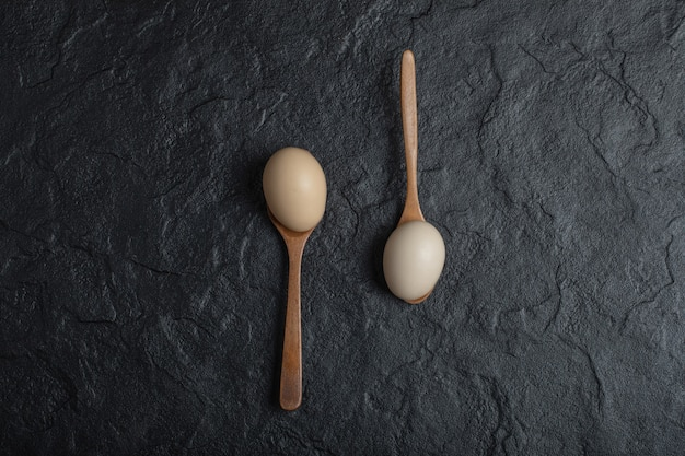 Two fresh chicken eggs on wooden spoons.